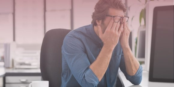 Man sitting at desk rubbing eyes stressed out due to poor mental health
