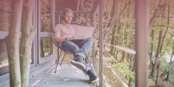 Man sitting outside while using laptop enjoying remote work benefits