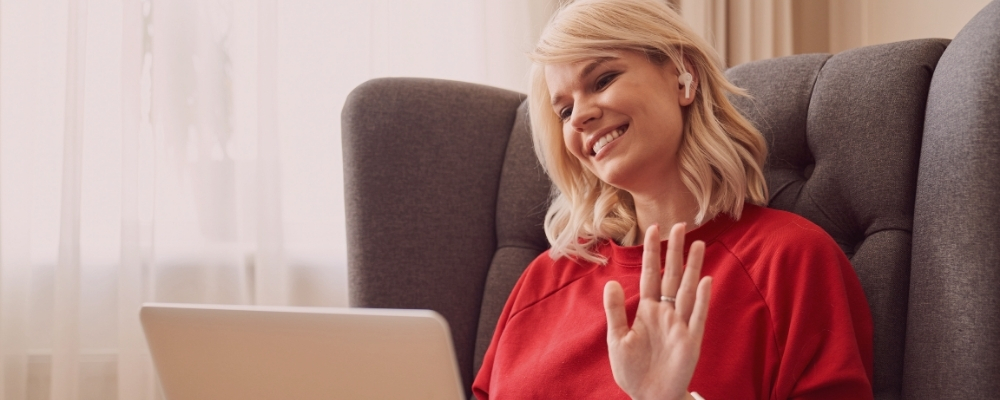 Emotionally intelligent female manager waving to video camera while on a call with burnt out direct report
