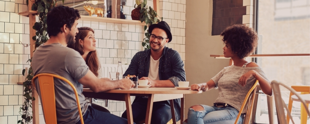 Team members meeting in person at a coffee shop to get to know one another