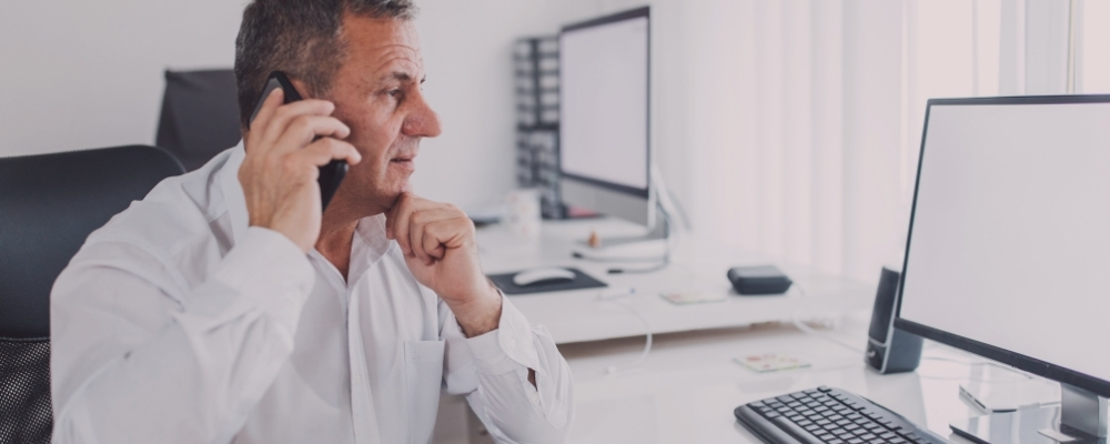 Male senior manager on the phone with a direct report helping to navigate burnout resolution