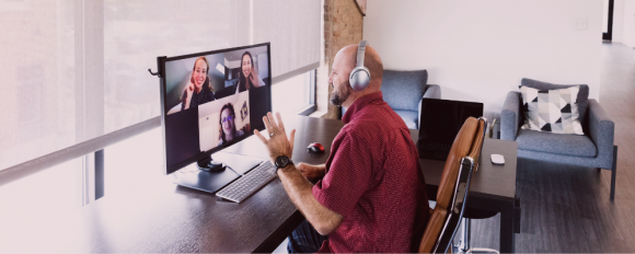Multiple remote employees engaging in a video chat with emphasis on man seated at desk waving to the camera