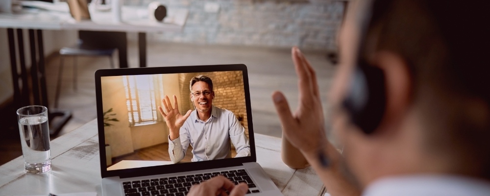 Two male remote employees on a video call to help reach a burnout resolution