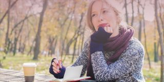 Woman wearing a scarf and drinking coffee in the park as she writes in a journal