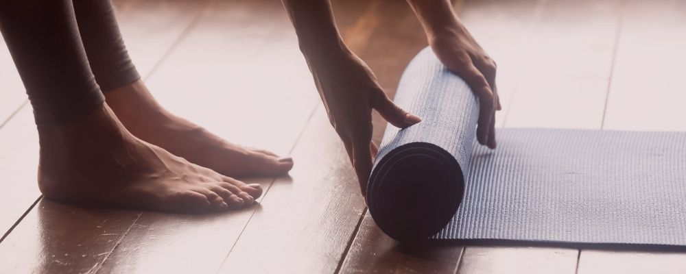 Woman unrolling a blue yoga mat onto a hardwood floor