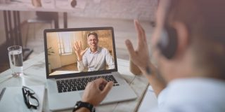 Remote employee waving to another worker through video conferencing to celebrate going remote
