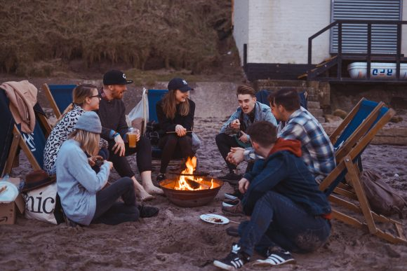 Employees gathered around a fire on the beach for a remote team retreat