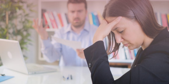 Woman holding her head and looking upset while manager makes a scene
