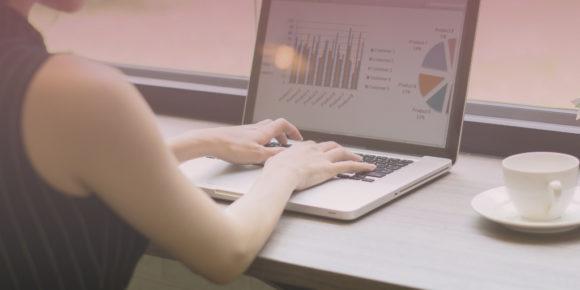 Woman typing on laptop that displays remote work statistics