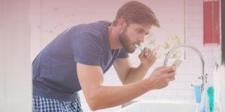 Man in blue shirt brushing his teeth while posting on social media