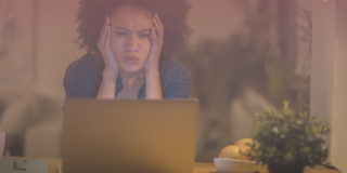 Woman holding her face in frustration as she stares at laptop trying to avoid conversations remotely