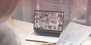 Woman looks over meeting notes while on a video call with multiple team members