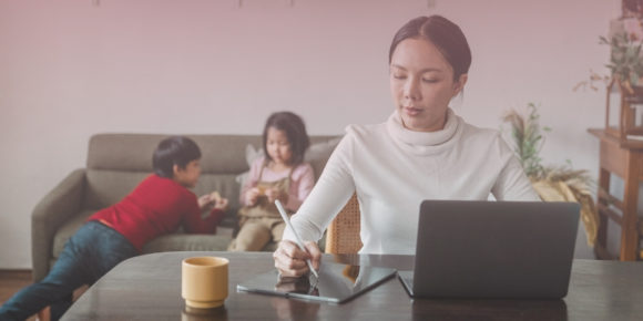 Woman in white shirt drawing on tablet for work while children play behind her